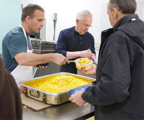 Volunteers serving food to the homeless