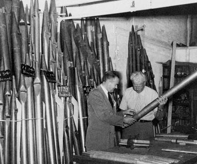 Two men examining organ pipes